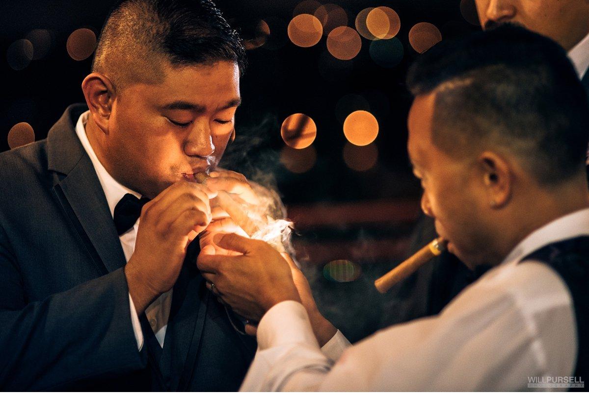 groom smoking cigar wedding